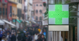 Pharmacy sign with green cross in busy street Footage
