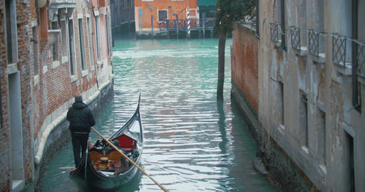 Veteran Gondolier Rowing Gondola along Water Canal in Venice, Italy Footage