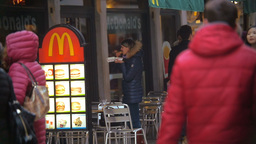 Woman Eating Fast Food by the Entrance to Restaurant Footage