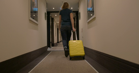 Woman with suitcase walking in hotel corridor Footage