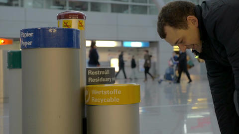 Man throwing plastic water bottle in recycle bin Footage