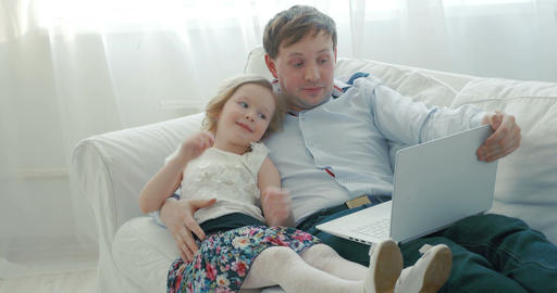 Father and daughter using laptop on the sofa Footage