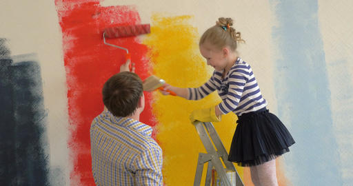 Father and daughter painting walls in bright colors Footage