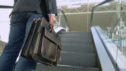Businessman with leather briefcase riding on escalator Footage