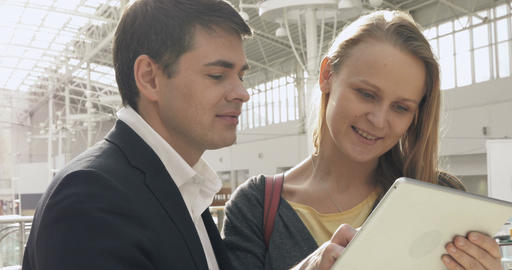 Young happy man and woman talking on business with pad Footage