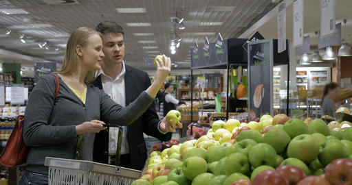 Young people choosing apples in the supermarket Footage