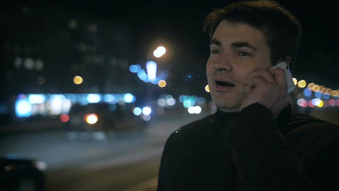 Man having phone conversation outdoor in night city Footage