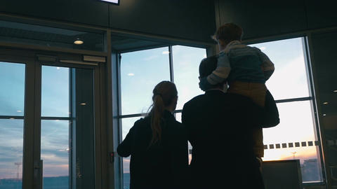 Young family looking out airport window at sunset Footage