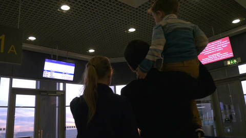 Family at airport terminal looking outside at sunset Live Action