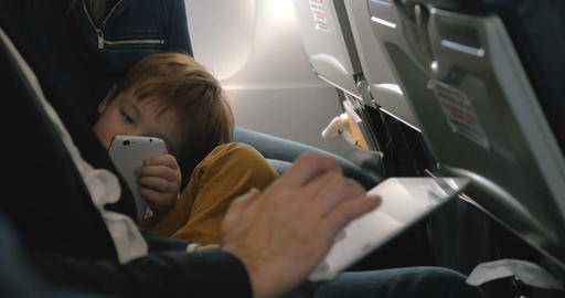 Child with cell and and man using pad in plane GIF