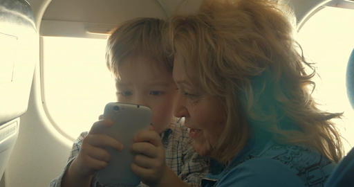 Child and grandmother entertaining with phone in plane Footage