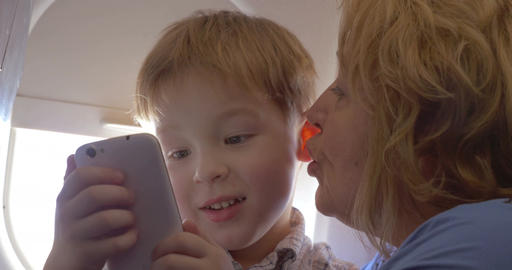 Grandmother talking to grandson in the plane Footage