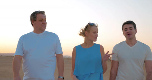 Three people enjoying evening walk on the beach Live Action