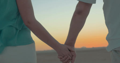 Man and woman take hands on the beach Live Action