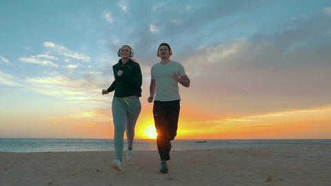 Young Couple Jogging on the Beach Footage