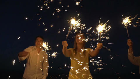 Family with sparklers on the beach at night Footage