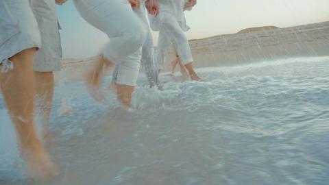 Four people splashing sea water with feet Footage