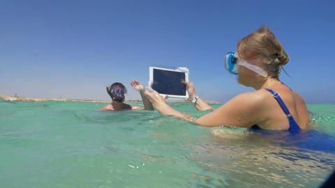 Woman and man in the sea making vacation photos with pad Footage