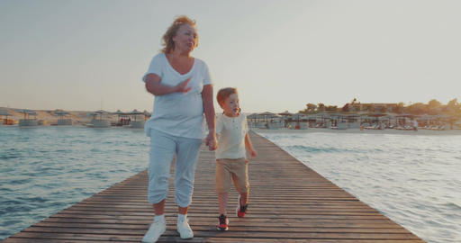 Grandmother and grandson having outdoor walk on resort Footage
