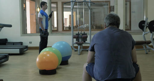 Man exercising with weight disks, his friend having a rest Footage