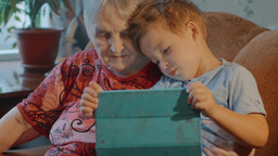 Grandmother and grandson use tablet at home Footage