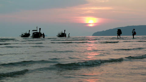 Time-lapse of travelers wading towards wooden long-tail boats floating near a to Footage