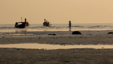 Wooden long-tail boats floati near a tourist beach at sunset time, people walkin Live Action