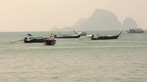 Wooden long-tail boats are floating near a tourist beach in Ao Nang, Krabi, Thai Live Action