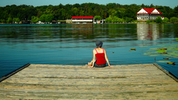 Girl With Sun Hat Dipping Her Feet In Lake And Looks Into The Distance Footage