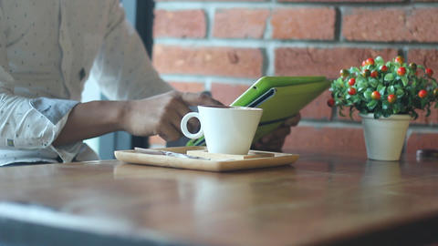 man with tablet computer drinking coffee in cafe Footage