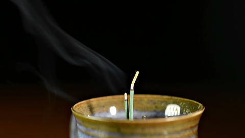 Incense sticks burning in pottery pot Footage