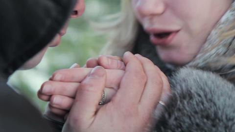 boyfriend warms hands sweetheart, frozen in the cold Footage