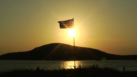 Greek flag on a coast before sunset Greece Footage