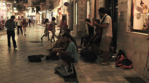 young group play traditional greek music among people in shopping island street Footage