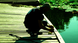 Fishing on the lake.Silhouette of fisherman preparing rod and bait for fishing Footage