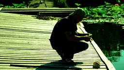 Fishing on the lake.Silhouette of fisherman preparing rod for fishing Footage