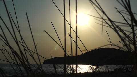 Sunset Across A Beach And Behind Grass And Island - Zoom In stock footage