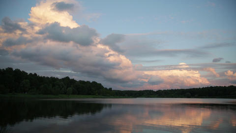 Evening landscape with the lake and pink clouds lit with the sun on a sunset Footage