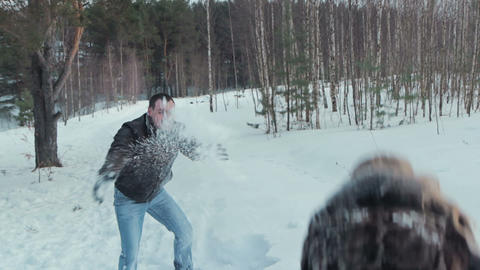 Young couple having snowball fight and kiss Footage