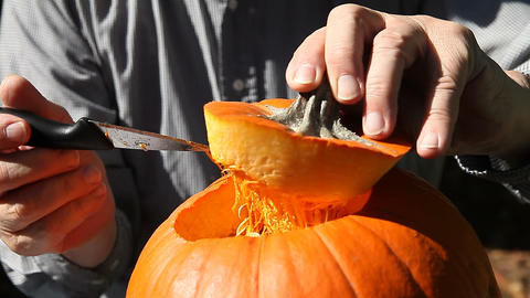 Man cuts opening on Halloween pumpkin Footage