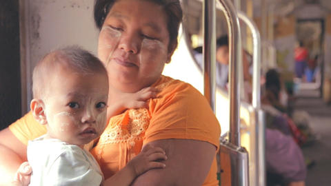 Myanmar train - mother holds baby facepaint Footage