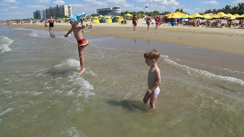 Boy with girl jumping on the waves Footage