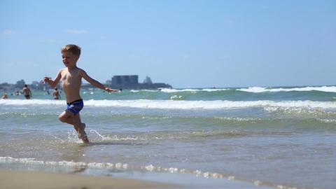 Little boy running through the waves Footage
