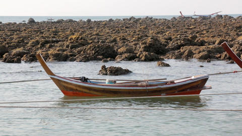 Small wooden rowing boat floats at a shore in Thailand Live Action