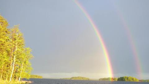 Tilt shot of rainbow over lake Footage