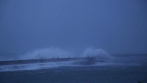 Waves breaking against barrier wall at nighttime Footage