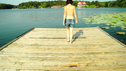 Woman in Shorts Walks On Wooden Pier, She Undressed Then Jumps In The Lake Footage
