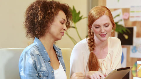 Smiling casual businesswomen brainstorming with tablet Footage