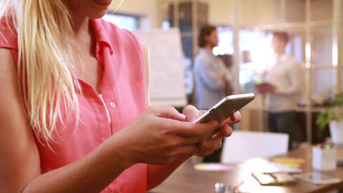 Smiling casual businesswoman texting in front of colleagues Footage