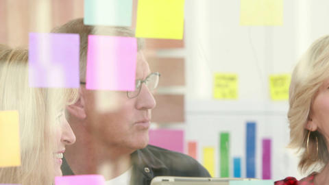 Businessman writing on post it with his colleagues Footage